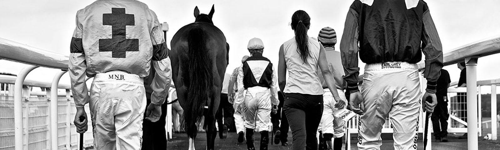 Group of jockeys walking towards a track.